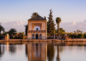 Saadian pavilion,Menara gardens and Atlas in Marrakech, Morocco, Africa at sunset. Water reflection.